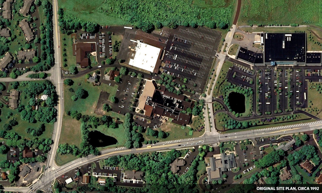 Aerial view, circa 1992, shows two suburban mall buildings set back from all roads.